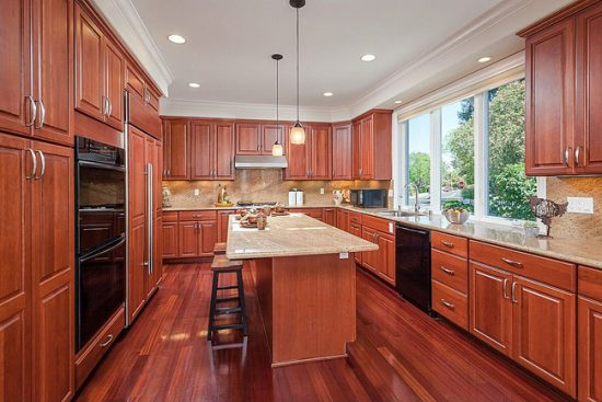Сочетание теракотового ламината и кухонной мебели из натурального древа