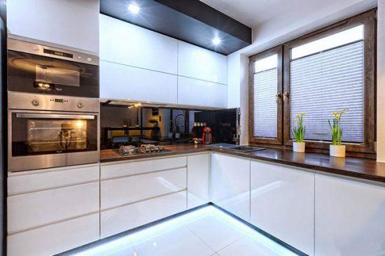 Зонировать пространство угловой кухни можно с помощью точечных светильников
